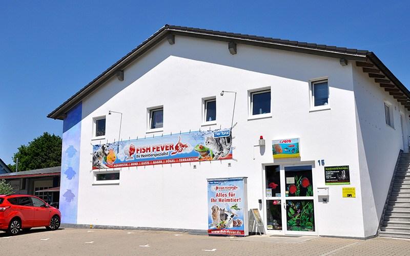 Fish Fever Ladengeschäft von außen mit großem Fish Fever Banner und Parkplatz vor dem Eingang
